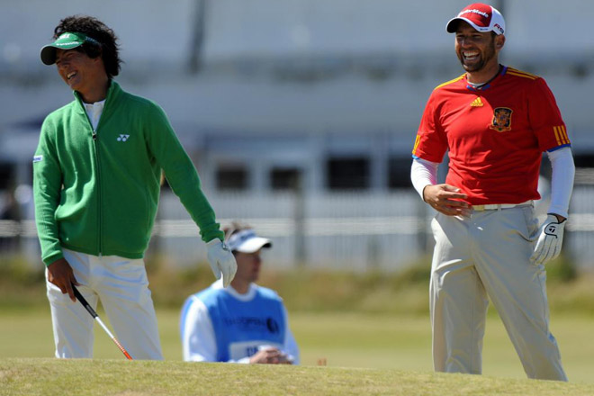 El gofista espa�ol Sergio Garc�a en presencia del Japon�s Ryo Ishikawa, se pone la camiseta de la selecci�n espa�ola durante el Open Golf Championship de St. Andrews (Escocia).