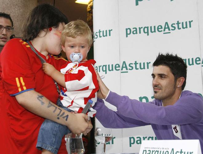 Villa firma la camiseta de un ni�o esportinguista en su visita a su pueblo natal, Tuilla