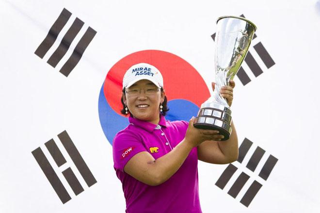 La sur coreana Jiyai Shin, posa con el trofeo de campeona del 17th Torneo Evian Masters de Golf, con la bandera de su pa�s a la espalda.