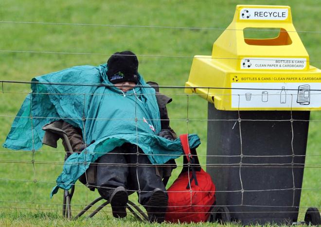 Un espectador del Gran Premio de Australia de motociclismo trat�ndose de guarecer de la lluvia durante los entrenamientos.