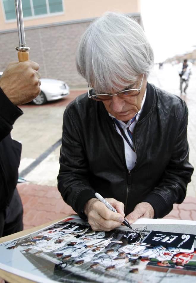 El patr�n de la F�rmula 1 firma un aut�grafo a un aficionado en el circuito de Yeongam.