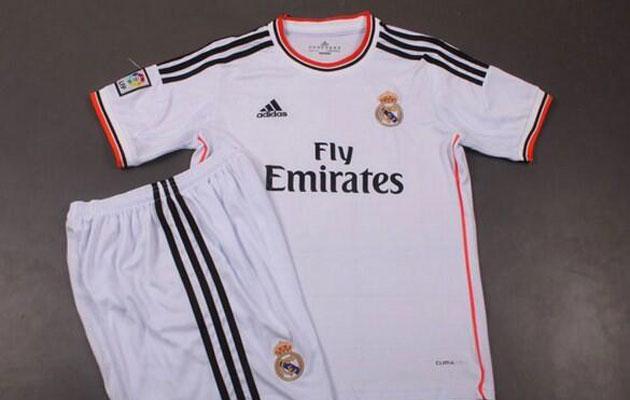 De la primera equipaci�n del Real Madrid para la temporada 2013-2014 destaca la raya naranja que bordea cuello y lateral de la misma y tambi�n, como en el resto de camisetas, el nuevo patrocinador, Fly Emirates.