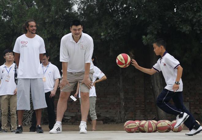 Joakim Noah (Chicago Bulls) y el ex jugador Yao Ming ense�ando baloncesto a los hijos de una comunidad de emigrantes de las afueras de Pek�n.