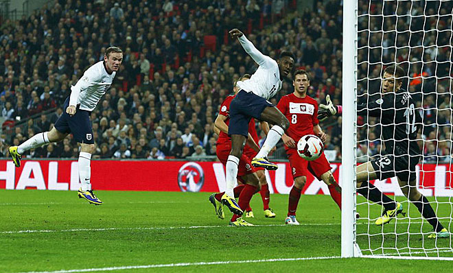 England's Wayne Rooney heads the ball to score at the Wembley Stadium.