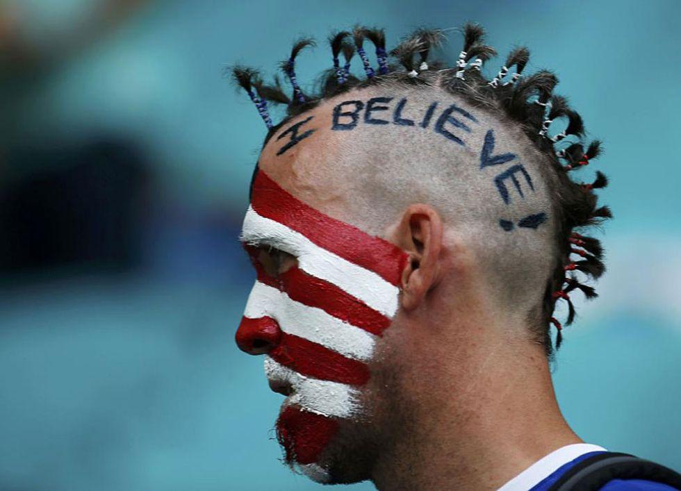 Un aficionado estadounidense con la expresión '¡Yo creo!' pintada en la cabeza.