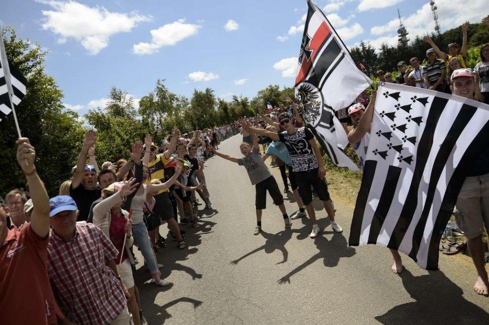 Lugareños bretones al paso de la carrera exhiben con orgullo la bandera de su región.
