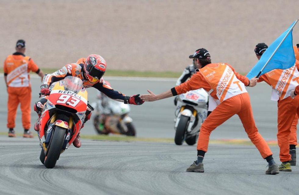Márquez choca la mano a un comisario tras acabar la carrera.