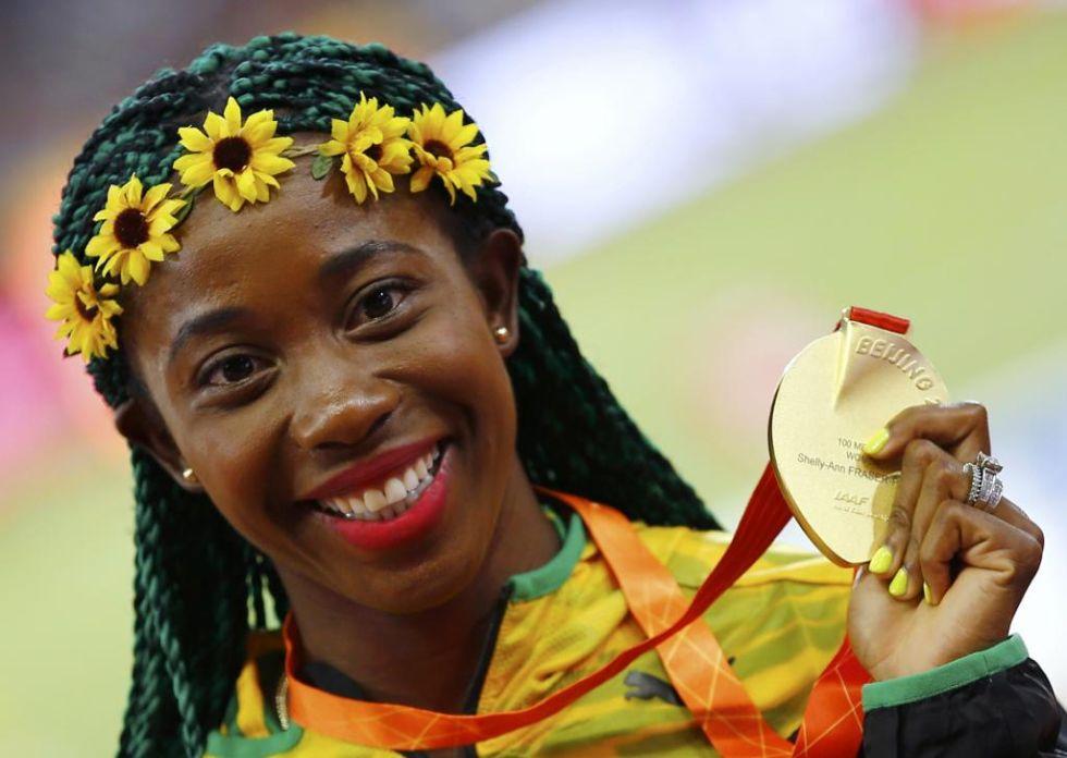 Con su eterna sonrisa, la jamaicana Fraser-Pryce ense�a al mundo la medalla de oro que consigui� ayer en Pek�n.