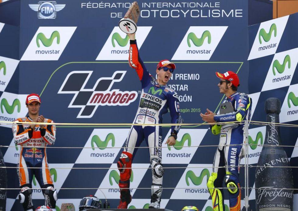 Jorge Lorenzo, exultante en el podio mientras aplauden Pedrosa y Rossi.