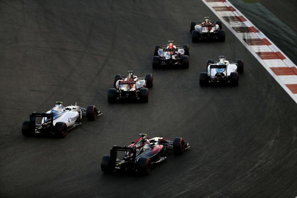 Varios coches toman una curva.