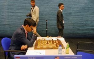 Giri se piensa la jugada, con Caruana de pie.