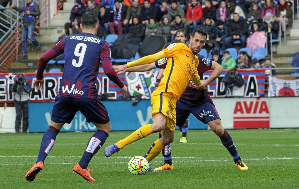 Busquets se zafa de la presión de dos jugadores del Eibar.