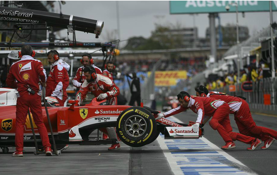 Técnicos de Ferrari empujan a Raikkonen dentro de su box en la...