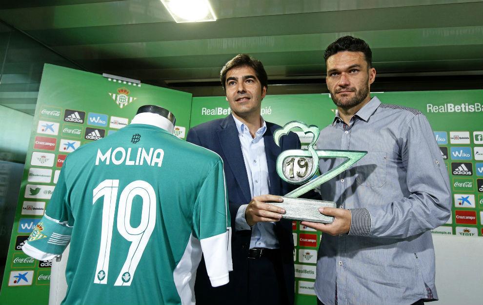 Jorge Molina recibe de manos de Ángel Haro una escultura, y posan...