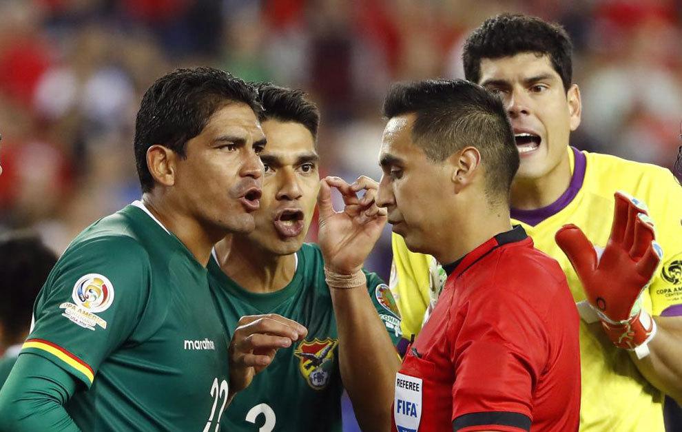 Los jugadores de Bolivia se quejan al árbitro tras el penalti.