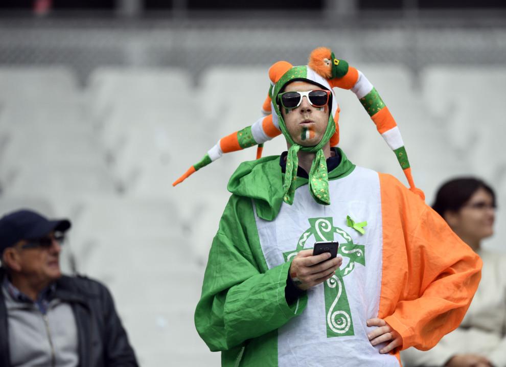 Un aficionado de Irlanda, ataviado con los colores de su selección y...
