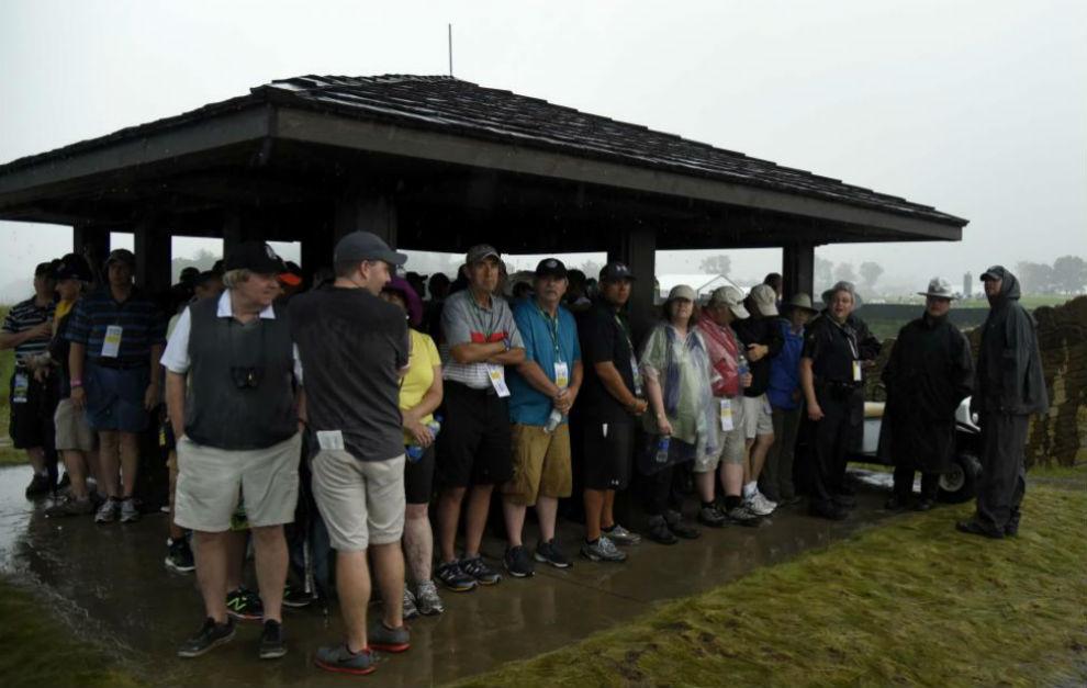 Un grupo de aficionados se refugia de la lluvia en el campo de...