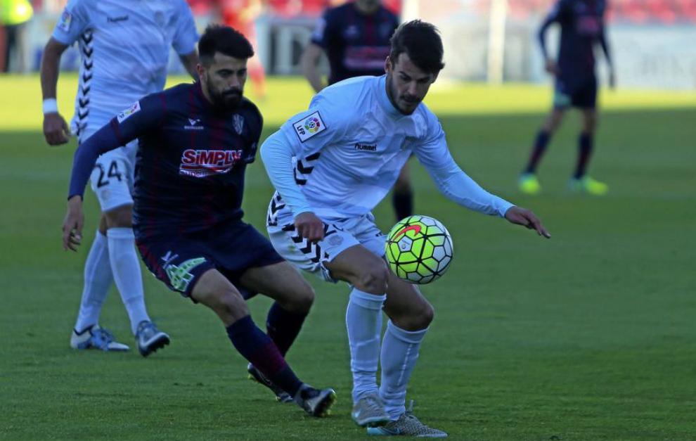 Edu Oriol disputa un balón ante un jugador del Huesca.