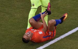 Alexis Sánchez quejándose del dolor en su tobillo.