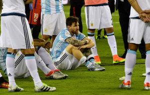 Messi mira con tristeza sentado en el césped tras perder la final...