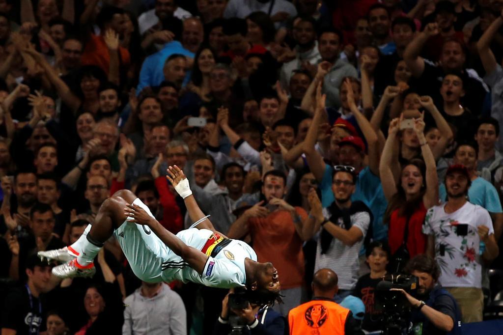 Michy Batshuayi celebrando un gol y al fondo la afición belga.