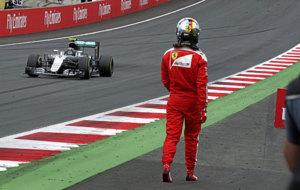 Vettel regresa al box caminando tras el accidente, mientras ve pasar a...
