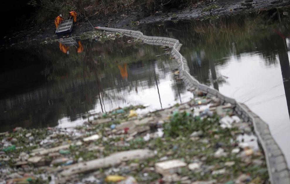 Operarios limpiando el río Meriti River que desemboca en la Bahía...