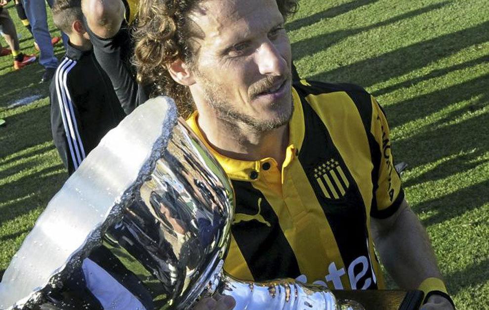 Forlán sostiene el trofeo de campeón.