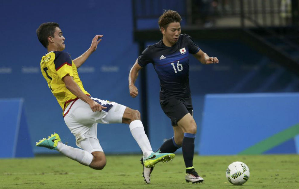 Takuma Asano trata de eludir la entrada de Felipe Aguilar.