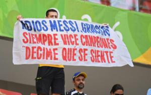 Una aficionado brasileño, con una pancarta en el choque ante...