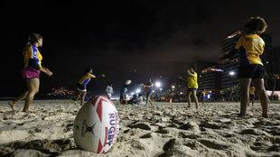 Varias niñas que viven en favelas juegan al rugby en la playa de...