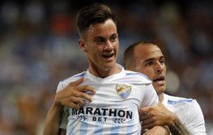 Juanpi es sujetado por un compa�ero en el festejo de su gol.