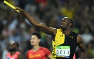 Bolt saluda con el testigo tras entrar en meta