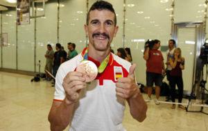 Carlos Coloma enseña su bronce en su llegada a Barajas.