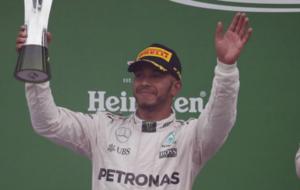 Hamilton saluda a los aficionados en el podio tras recibir el trofeo...