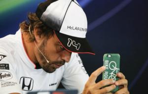 Alonso observa su smartphone durante una rueda de prensa