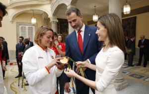 Mireia Belmonte ense�ando las medallas a los reyes