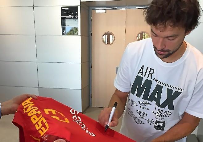 Sergio LLul firmando su camiseta de la selección española