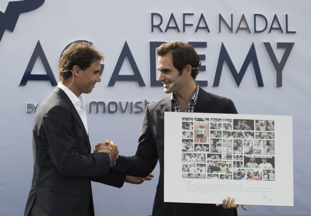 Roger Federer recibe el cuadro de regalo por parte de Nadal.