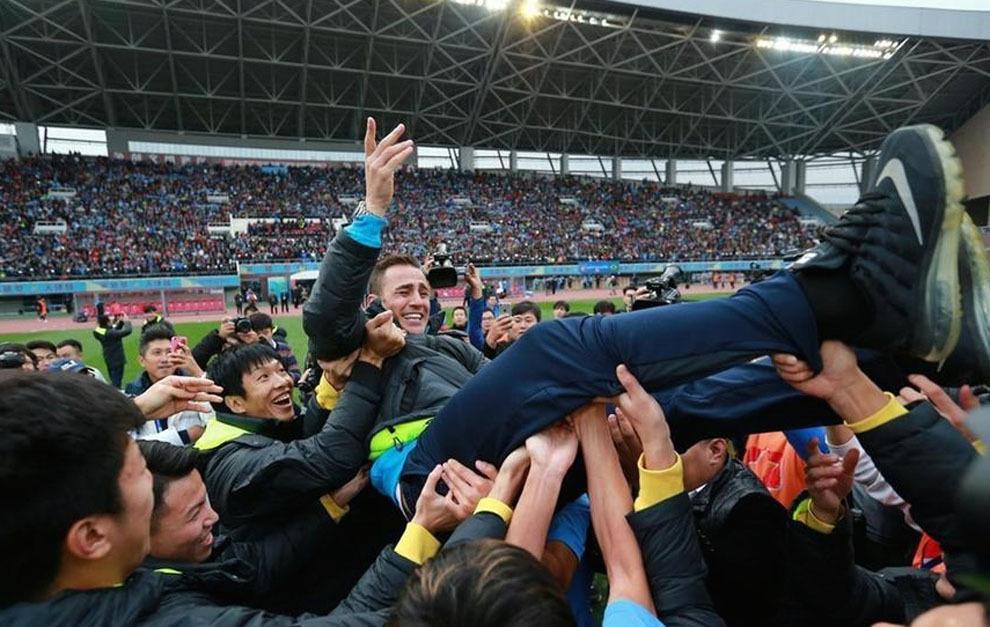 Cannavaro es levantado por los jugadores a pie de césped tras el...
