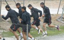 Los jugadores del Sevila corren para resguardarse de la lluvia en el...