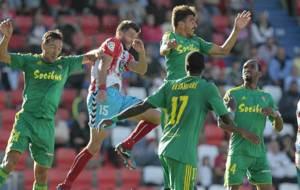 El central local Dealbert salta rodeado de jugadores del Cádiz