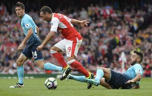 Santi Cazorla evita la entrada de Neil Taylor ante el Swansea.