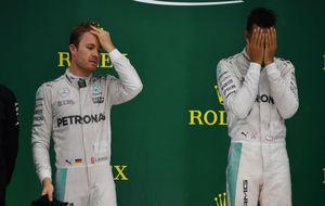 Rosberg se atusa el pelo y Hamilton se seca el sudor de la cara en el...