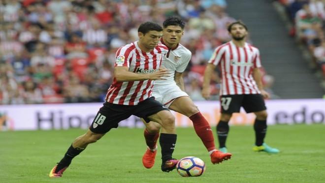 De Marcos conduce un balón ante la mirada de Correa
