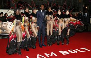 El atleta posa con un grupo de bailarinas en la alfombra roja.