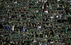 Aficionados del Chapecoense muestran bufandas verdes.