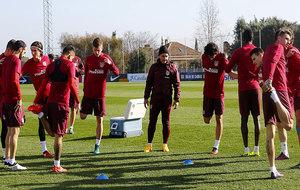 Los jugadores del Atlético estiran en el entrenamiento de este...