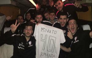 Los jugadores del Santiago posan con una camiseta en el autobús tras...