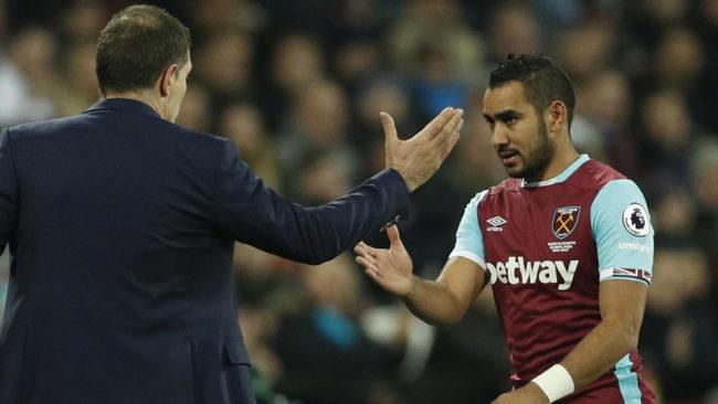 Dimitri Payet a punto de chocar la mano con su entrenador Slaven...